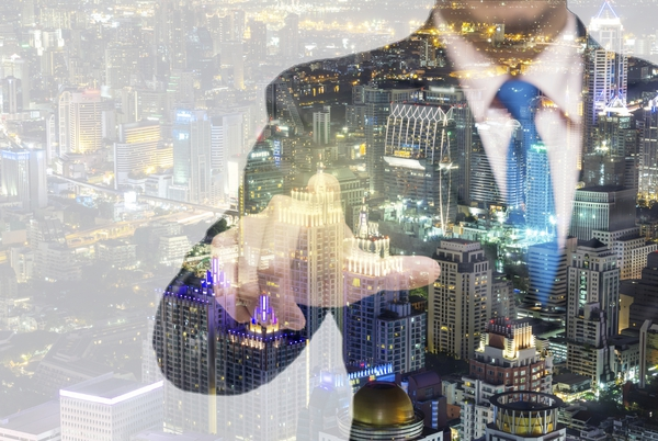 Double exposure of businessman with cityspace vision